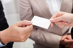 Businesspeople exchanging cards over coffee Royalty Free Stock Image