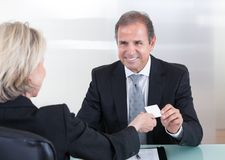 Businesspeople Exchanging Visiting Card In Office Royalty Free Stock Photos