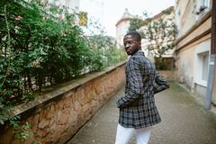 Businesspeople, fashion and modern urban lifestyle concept. Well. Fashion portrait of black african american man on  jacket and coat cloak on his shoulders Stock Image
