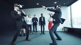 Businesspeople fighting in office in vr headsets. Two colleagues in helmets of virtual reality fight at office against the background of the applauding stock video footage