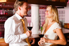 Businesspeople flirting in hotel bar. Two (casual) business people in a hotel bar in the evening having glasses of red wine and a little flirt stock photography