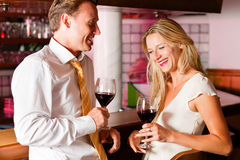 Businesspeople flirting in hotel bar. Two (casual) business people in a hotel bar in the evening having glasses of red wine and a little flirt stock photos