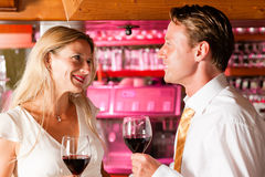 Businesspeople flirting in hotel bar. Two (casual) business people in a hotel bar in the evening having glasses of red wine and a little flirt stock photo