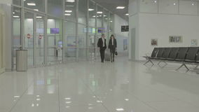 Businesspeople går i flygplatskorridoren arkivfilmer