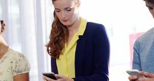 Businesspeople gebruikend mobiele telefoon stock video