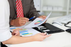 Businesspeople With Graphs At Office Desk Royalty Free Stock Photo