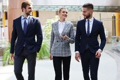 Businesspeople group walking at modern bright office interior.  stock photography