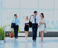 Businesspeople group walking at modern bright office interior. royalty free stock images