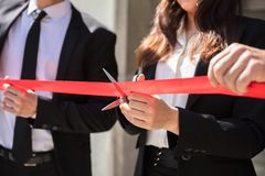 Businesspeople Hand Cutting Red Ribbon. Close-up Of Businesspeople Hand Cutting Red Ribbon With Scissors royalty free stock photos