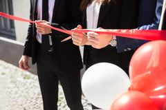 Businesspeople Hand Cutting Red Ribbon stock photos