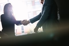 Businesspeople hand shake after a deal. Businesswoman shaking hands with businessman after a successful agreement in office meeting. Businesspeople hand shake royalty free stock photography