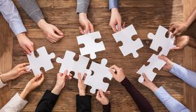 Businesspeople Hand Solving Jigsaw Puzzle Royalty Free Stock Photo
