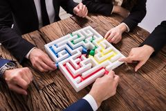 Businesspeople Hand Solving Maze Together stock photo