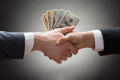 Businesspeople hands with money. Close-up Of Two Businesspeople Shaking Hands With Money stock photo