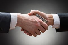 Businesspeople hands with money. Close-up Of Two Businesspeople Shaking Hands With Money stock image