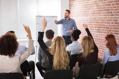 Group Of Businesspeople Raising Hands In Conference. Businesspeople With Hands Raised Answering Businessman In Conference At Office stock photography