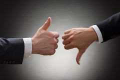 Businesspeople hands showing thumb up and thumb down. Close-up Of Two Businesspeople Hands Showing Thumb Up And Thumb Down Sign Royalty Free Stock Photo