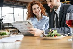 Businesspeople having business lunch at restaurant sitting eating salad drinking wine reading newspaper checking stock stock photo