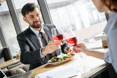 Businesspeople having business lunch at restaurant sitting near window drinking wine smiling happy royalty free stock photo