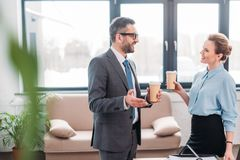Businesspeople having chit-chat while drinking coffee. At office royalty free stock photo