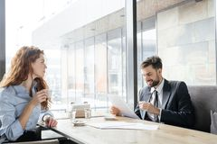 Businesspeople having coffee break at restaurant sitting drinking espresso man looking at documents joyful while woman stock image
