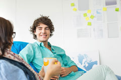 Businesspeople having coffee while relaxing on beanbag chairs in creative office Stock Photos