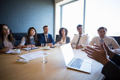 Businesspeople having a discussion in conference room Stock Image