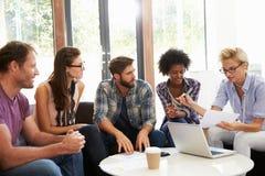 Businesspeople Having Informal Meeting In Modern Office Stock Photos