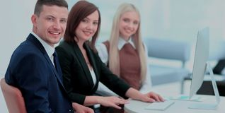 Businesspeople Having Meeting Around Table In Modern Office. Three business people sitting at seminar, the focus is on man Royalty Free Stock Photography