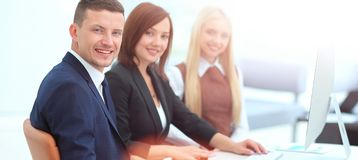 Businesspeople Having Meeting Around Table In Modern Office. Three business people sitting at seminar, the focus is on man Royalty Free Stock Images