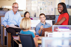 Businesspeople Having Meeting In Modern Open Plan Office. Smiling Stock Photos
