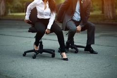 Businesspeople having racing on office chairs royalty free stock photos