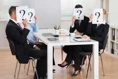Businesspeople Hiding Faces Behind Question Mark Sign. Group Of Businesspeople Hiding Faces Behind Question Mark Sign In Conference Room Stock Photo