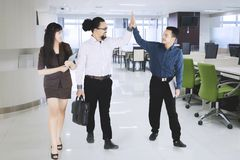 Businesspeople high five while entering a meeting room.  Royalty Free Stock Image