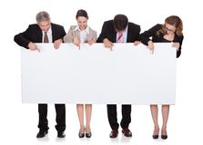 Businesspeople holding a blank banner Stock Images
