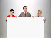 Businesspeople holding blank poster Stock Photos