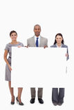 Businesspeople holding blank sign Stock Photos