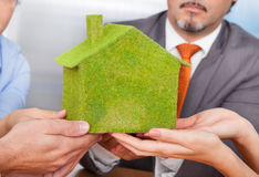 Businesspeople Holding Eco Friendly House. Close-up Of Business People's Hand Holding Eco Friendly Green House Over Desk Stock Photo
