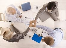 Businesspeople holding hands united. Over meeting table, while teamworking, high angle view Stock Image