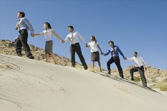 Businesspeople Holding Hands And Walking Uphill Royalty Free Stock Image