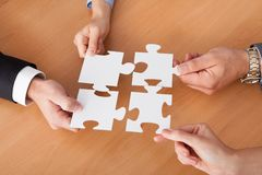 Businesspeople Holding Jigsaw Puzzle Royalty Free Stock Photos
