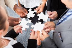 Businesspeople Holding Jigsaw Puzzle. Close-up Photo Of Businesspeople Holding Jigsaw Puzzle royalty free stock images