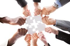 Businesspeople Holding Jigsaw Puzzle. Close-up Photo Of Businesspeople Holding Jigsaw Puzzle stock photos