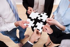 Businesspeople holding jigsaw puzzle Stock Photography