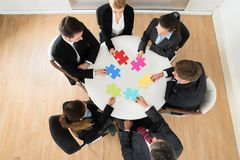 Businesspeople holding multi-colored jigsaw puzzle Stock Photography