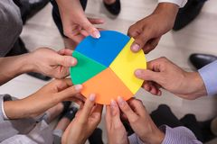 Businesspeople Holding Pie Chart. Elevated View Of Businesspeople Holding Multi Colored Pie Chart royalty free stock photo