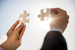 Businesspeople holding puzzle Stock Photography