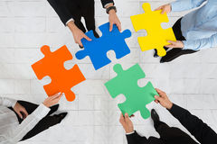 Businesspeople Holding Puzzle Pieces. High Angle View Of Businesspeople Team Holding Colorful Puzzle Pieces In Hands royalty free stock photo
