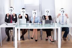 Businesspeople holding question mark in front of face Stock Images