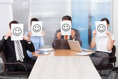 Businesspeople holding smiley icon Royalty Free Stock Image